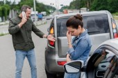 upset man and woman near cars after car accident