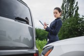 attractive businesswoman writing something to car insurance after car accident