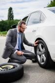 pohledný podnikatel změnu pneumatiky na auto na silnici