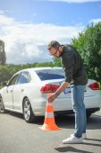 Fotografie handsome man holding car insurance and putting safety cones on road