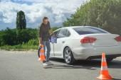 Fotografie pohledný muž drží auto pojištění a dopravní kužely na silnici