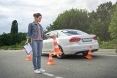 Fotografie driver holding car insurance and putting traffic cones on road