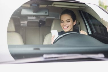 smiling attractive woman using smartphone while driving car