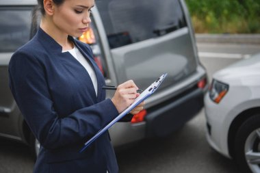 side view of attractive woman writing something to car insurance after car accident