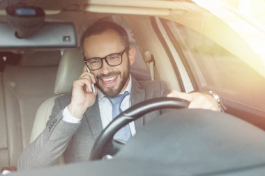 smiling handsome businessman driving car and talking by smartphone