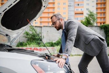 side view of handsome businessman leaning on open car hood