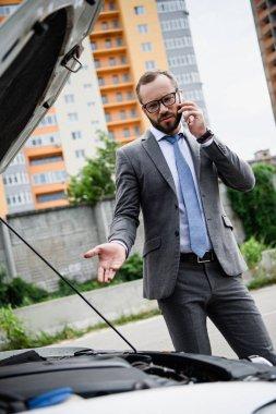 handsome businessman talking by smartphone near broken car with open hood