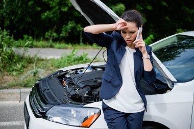 tired businesswoman talking by smartphone near broken car with open hood
