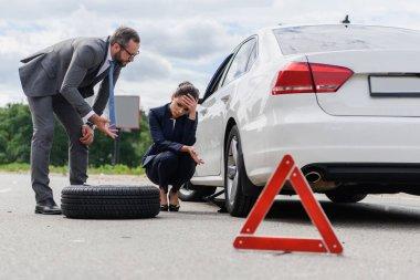 businessman gesturing and sad businesswoman squatting near broken car on road