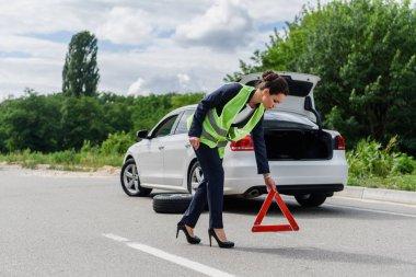 attractive businesswoman in light green vest putting stop sign on road near broken car