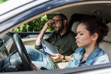 dissatisfied teacher touching forehead in car during driving test