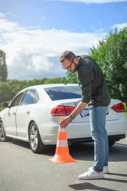 handsome man holding car insurance and putting safety cones on road