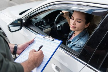 cropped image of driver waiting while man writing something to car insurance on road