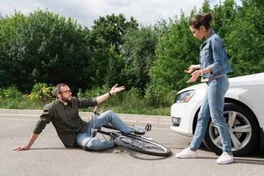 driver and biker quarreling after car accident on road