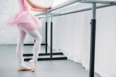 cropped shot of child in pink tutu exercising in ballet school