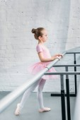 Fotografie side view of beautiful little ballerina practicing ballet in studio