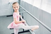 Fényképek adorable kid in pink tutu stretching and practicing in ballet school