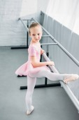 Fényképek high angle view of child in pink tutu exercising in ballet school