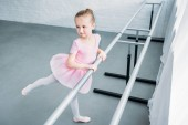 high angle view of adorable child practicing ballet in studio