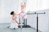 roztomilé dítě v růžové sukénce strečink a zatímco cvičí balet s učitelem při pohledu na fotoaparát