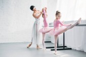 gyönyörű fiatal balett-tanár a gyerekek az iskolában balett gyakorló