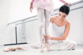 cropped shot of young ballet teacher training with little student in ballet school