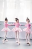 back view of graceful little ballerinas practicing ballet in studio