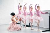mladá žena učí roztomilé děti tančí v baletní škole