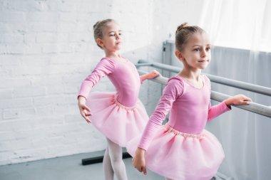 beautiful little kids in pink tutu skirts practicing ballet and looking away in ballet studio