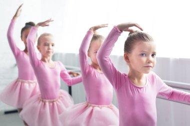 beautiful kids in pink tutu skirts dancing in ballet school