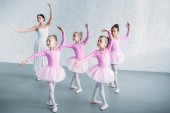 adorable kids in pink tutu skirts practicing ballet with young teacher in ballet school