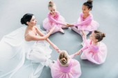 high angle view of little ballerinas and ballet teacher exercising together in ballet school
