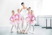 učitelka baletu s roztomilé malé baletky se usmívá na kameru v baletní škole