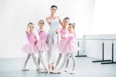 Fotografie little ballerinas and ballet teacher showing thumbs up and smiling at camera in ballet school