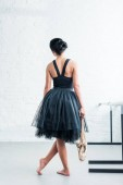 Fényképek back view of young ballerina holding pointe shoes while standing in ballet studio