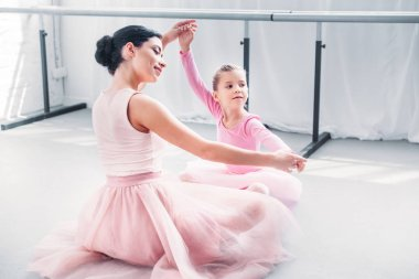 smiling young ballet teacher and little student in pink tutu skirts training together in ballet school