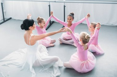 happy little ballerinas and ballet teacher sitting and holding hands in ballet school