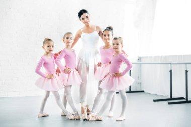 ballet teacher with cute little ballerinas smiling at camera in ballet school