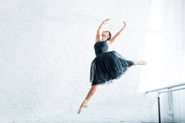 low angle view of beautiful young ballerina dancing in ballet studio