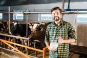 Fotografie hübscher Landwirt hält Krug Milch im Stall und Blick in die Kamera