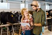 Lächelndes Bauernpaar mit Tablette im Stall bei Kühen