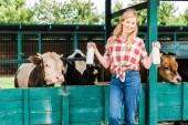 Fotografia beautiful farmer showing bottles of cow milk near stable