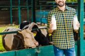 oříznutého obrázku usmívající se zemědělec lahví mléka poblíž stabilní