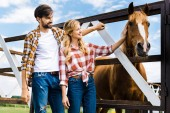 Photo couple of smiling farmers palming horse in stable