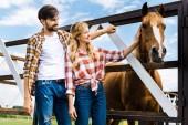 Fotografia coppia di agricoltori sorridenti palming cavallo in scuderia
