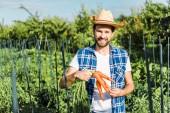 Fotografia bello coltivatore che tiene carote biologiche in campo presso azienda agricola sorridente