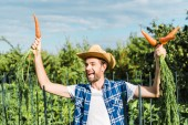 Fotografia happy handsome farmer showing organic carrots in field at farm