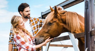 Couple of smiling ranchers palming horse in stable stock vector