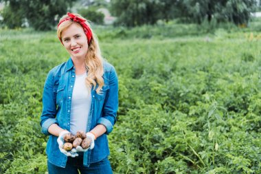 smiling attractive farmer holding ripe potatoes in field at farm and looking at camera