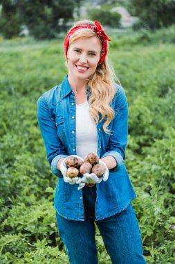 smiling attractive farmer holding ripe potatoes in field at farm
